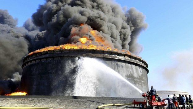 Fire-fighters work to put out the fire of a storage oil tank at the port of Es Sider in Ras Lanufon 29 December 2014