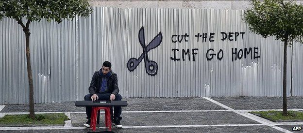 A man plays music in front of a sign saying IMF Go Home, Athens, 24 Feb 2015