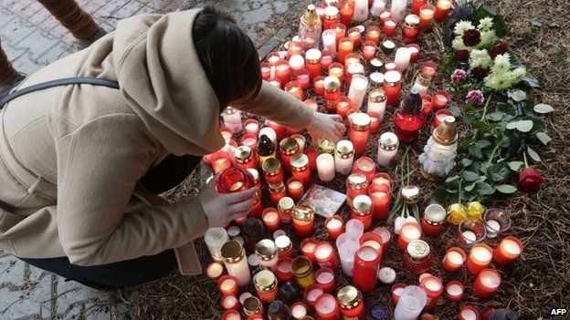 A woman places a candle on February 25, 2015 in front of a building where a gunman opened fire in a restaurant in Uhersky Brod, Czech Republic