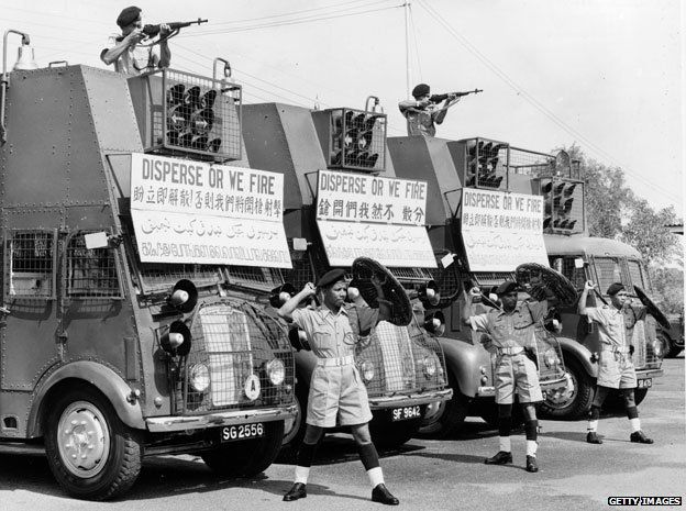 Members of the Singapore Police Riot Squad during race riots between Chinese and Malay groups in 1964. Their vehicles display warning signs reading 'Disperse Or We Fire'.