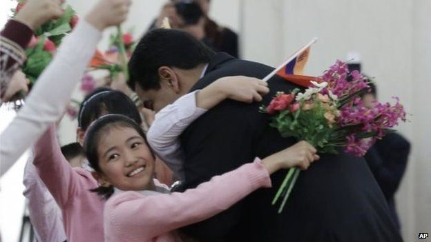 President Nicolas Maduro hugs a child during a welcome ceremony held by Chinese President Xi Jinping at the Great Hal in Beijing on 7 January, 2015.