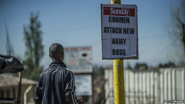A man stands next to a newspaper advertising in Maseru, Lesotho