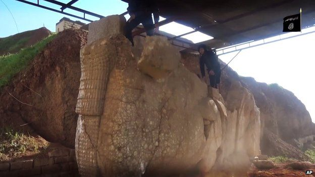 IS militant climbing on top of a statue at the Nerghal Gate, Mosul.