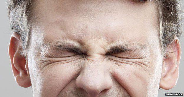 A man shutting his eyes tightly