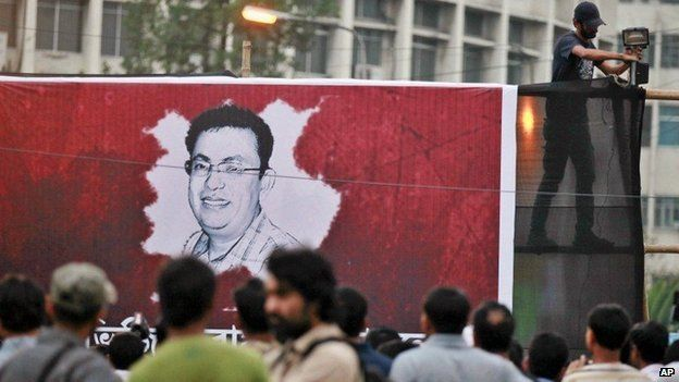 A Bangladeshi activist sets up a light on a poster displaying a portrait of Avijit Roy as others gather during a protest against the Roy in Dhaka, Bangladesh, Friday, Feb. 27, 2015.