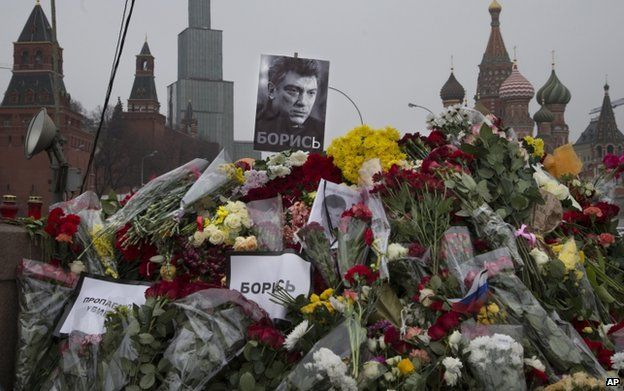 """Placards reading """"Propaganda kills"""" and """"Fight on!"""" were mixed with flowers near the Kremlin"""