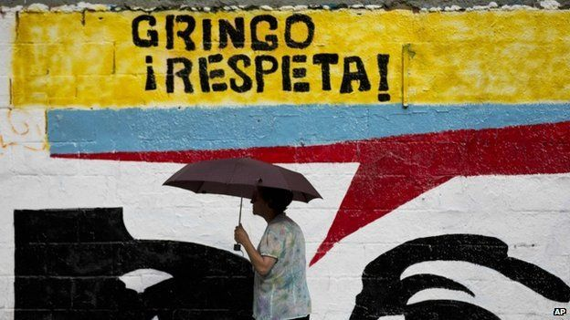 """A woman using an umbrella during a drizzle walks by a mural representing the eyes of Venezuela's late President Hugo Chavez that reads in Spanish """"Gringo, respect!"""" in Caracas, Venezuela, Monday, March 2, 2015."""