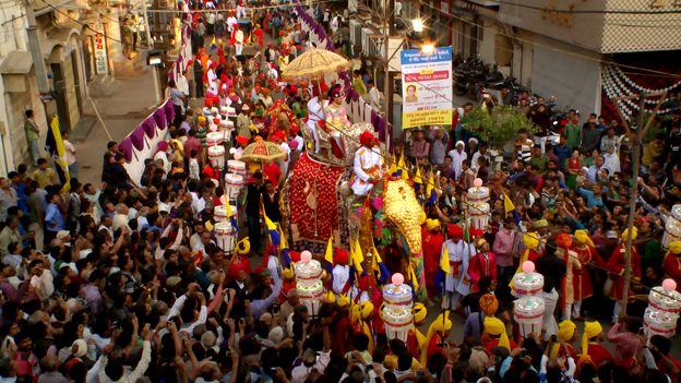 Prince on an elephant surrounded by crowds