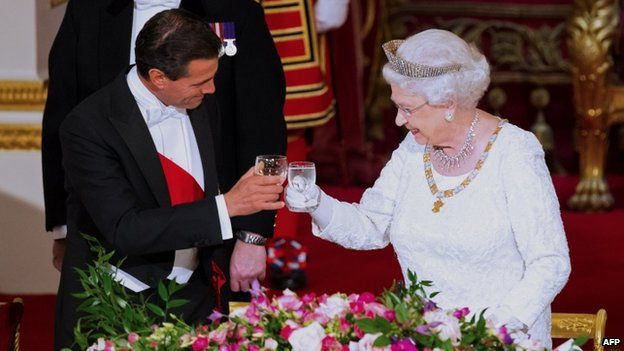 Mexican President Enrique Pena Nieto raises his glass in a toast with the Queen
