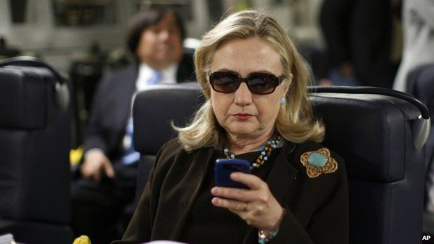 Former Secretary of State Hillary Rodham Clinton checks her Blackberry from a desk inside a C-17 military plane upon her departure from Malta, in the Mediterranean Sea, bound for Tripoli, Libya