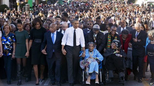 """President Barack Obama walks holding hands with Amelia Boynton, who was beaten during """"Bloody Sunday,"""" as they and the first family and others walk across the Edmund Pettus Bridge in Selma, Alabama on 7 March 2015."""