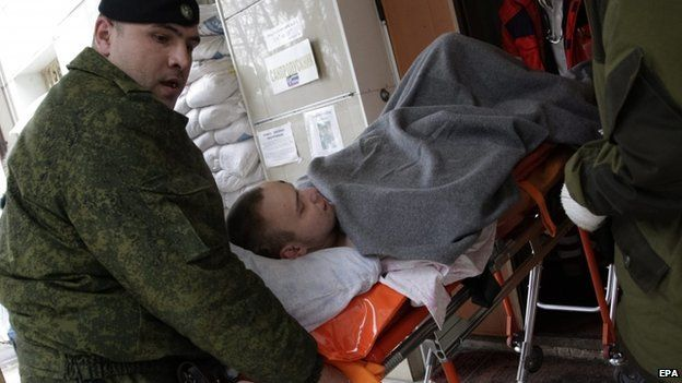 Separatist rebels carry an injured comrade from hospital to an ambulance as they prepare to send injured separatists to Russian town Rostov from Donetsk