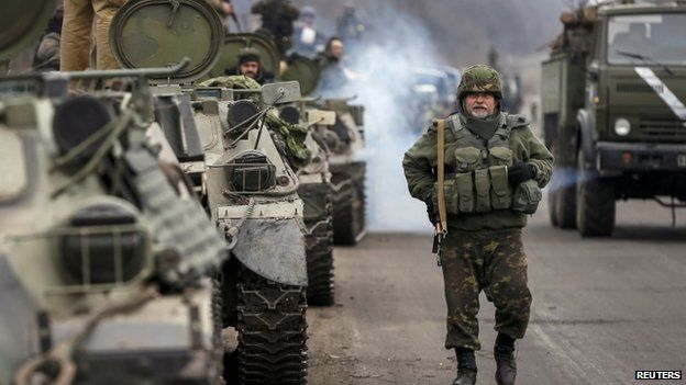 Members of the Ukrainian armed forces and armoured personnel carriers preparing to pull back from Debaltseve region