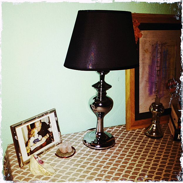 A table with a picture frame, lamp and red bangle