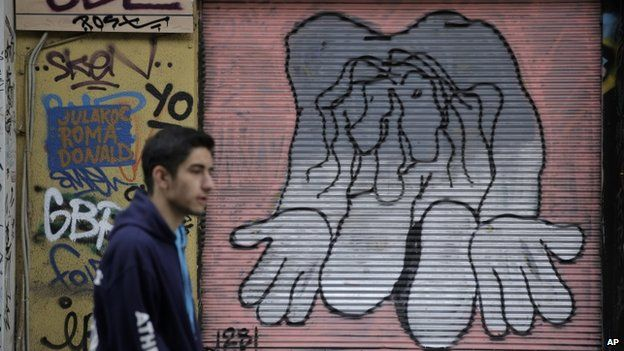 A man walks past a shop with its shutter painted with a mural, in central Athens on Monday, 9 March 2015