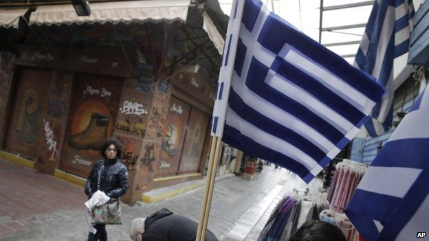 Greek flags fly as a tourist walks by a souvenirs shop in Athens on Monday, 9 March, 2015