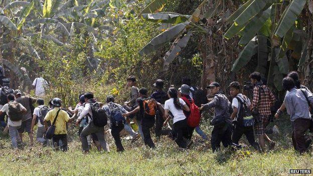 Reporters run to a safe place during violence in Letpadan 10 March 2015.