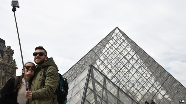 Tourists use selfie stick outside The Louvre