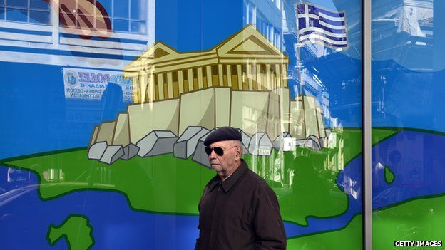 A man walks past a shop window in Athens, with a display of the Acropolis