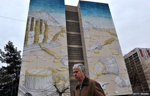 Man walks past graffiti of Acropolis collapsing in Thessaloniki (5 March)
