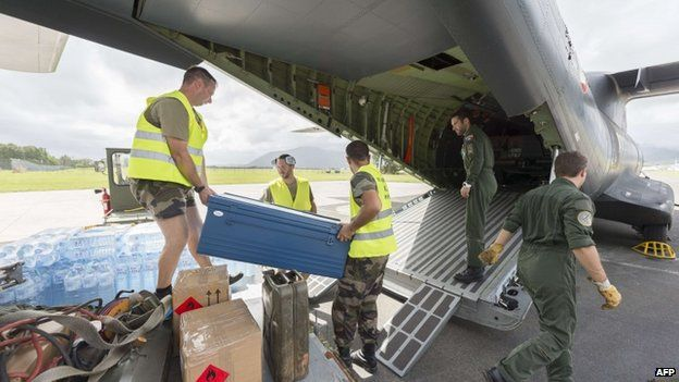 Privates load water bottles and other relief into a French Army logistical transport plane bound for Vanuatu, at the Aerial Military Base Lieutenant Paul Klein (formerly known as La Tontouta), north of Noumea, New Caledonia, on 15 March 2015