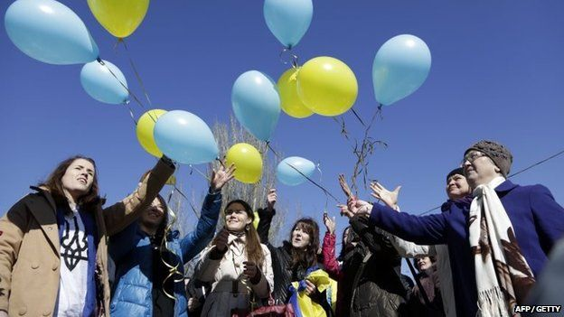 People release balloons in the colours of the Ukrainian flag during a rally marking the anniversary of Ukrainian poet Taras Shevchenko 1814-1861, in Simferopol, on 9 March 2015