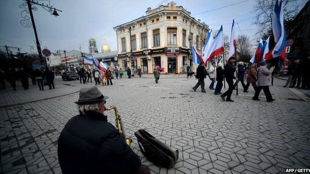 A man playing a saxophone as people waving Russian and Crimean flags walk to a pro-Russia rally in Simferopol's Lenin Square on 9 March 2014