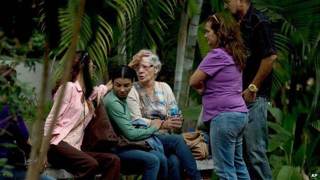 Josefa Alvarez de Gonzalez, centre, is consoled by relatives of her husband outside the morgue in Caracas