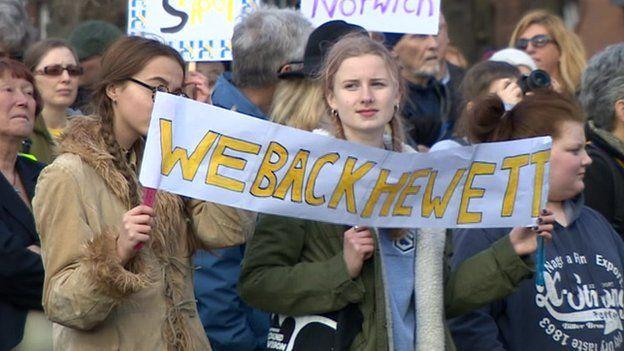 Protestors carry We Back Hewett sign
