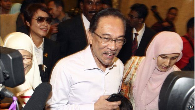 In this Tuesday, 10 Feb 2015 file photo, Malaysian opposition leader Anwar Ibrahim, center, arrives at court house in Putrajaya, Malaysia.
