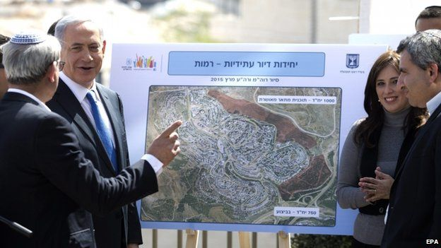 Israeli Prime Minister Benjamin Netanyahu (2-L) looks at future construction plans during a campaign stop at the sprawling south Jerusalem Jewish neighborhood of Har Homa