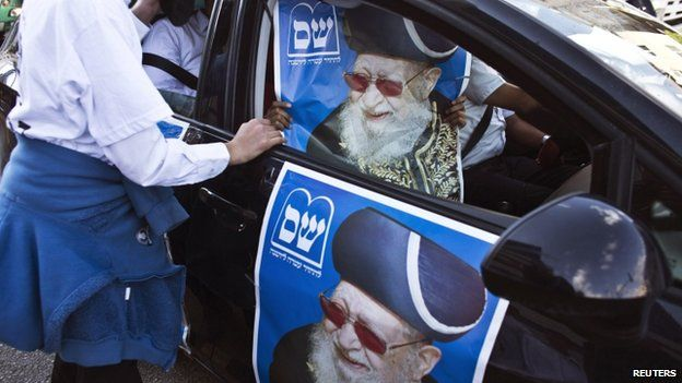 """A supporter of the ultra-Orthodox Shas party, or Sephardic Torah Guardians, holds a campaign poster depicting the party""""s spiritual leader Rabbi Ovadia Yosef, in Bnei Brak near Tel Aviv March 16, 2015"""