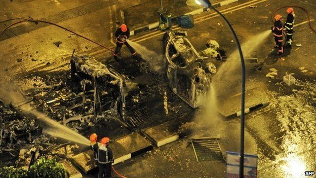 Firemen douse a charred ambulance after a riot broke out in Singapore, in the early hours of December 9, 2013