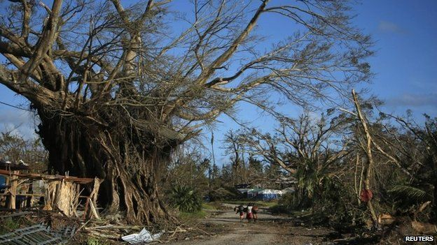 People walk through a street in Lenakel town after Cyclone Pam in Tanna, about 200 km from Port Vila, capital city of the Pacific island nation of Vanuatu March 17, 2015