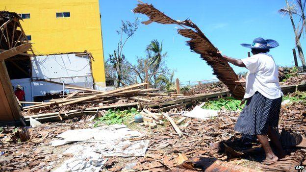 A resident cleans up cyclone damage in Vanuatu's capital Port Vila (17 March 2015)