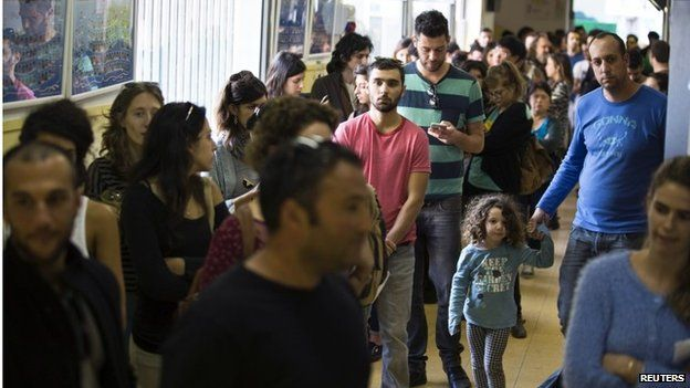 Israeli voters wait in line at a polling station in Tel Aviv