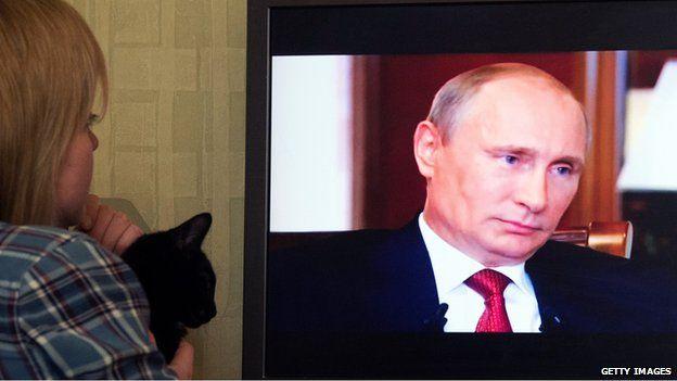 Woman watches Russian President Vladimir Putin (15 March)