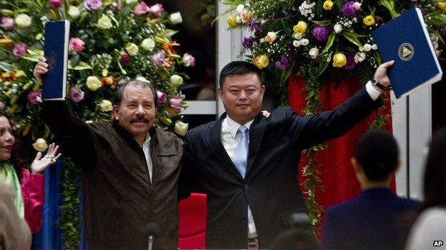 In this file photo taken on 14 June, 2013, Chinese businessman Wang Jing holds up a concession agreement for the construction of a multibillion-dollar canal at the Casa de los Pueblos in Managua