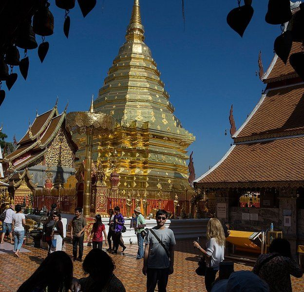 A traveller poses for a picture at Wat Doi Suthep temple in Chiang Mai, where Chinese tourists have been accused of bad behaviour