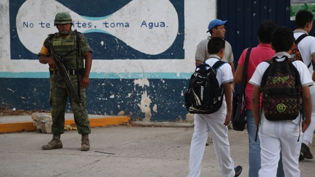 A soldier watches as children arrive for school in March 2015