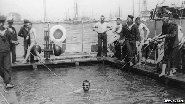 1910: Naval cadets receiving swimming lessons