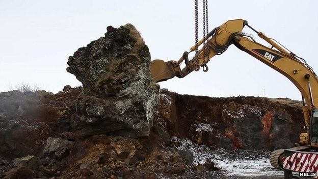 A crane is used to move a rock in Iceland thought to be an elf church to make way for a new road on 18 March.