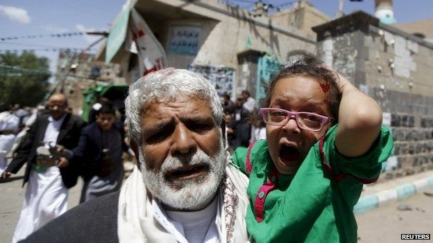A man carries a wounded girl after a suicide bomb attack on a mosque in Sanaa, Yemen (20 March 2015)
