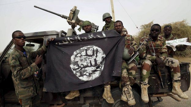 Nigerien soldiers hold up a Boko Haram flag that they had seized in the recently retaken town of Damasak