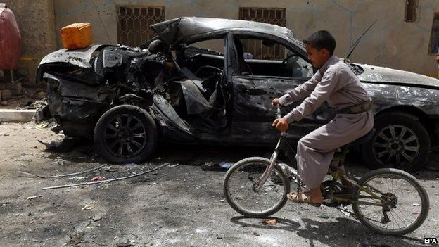 A Yemeni boy on a bicycle rides past a destroyed car in downtown Sanaa, Yemen, 21 March 2015,