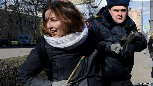 A woman opposed to a far-right forum in St Petersburg is removed by police, 22 March 2015