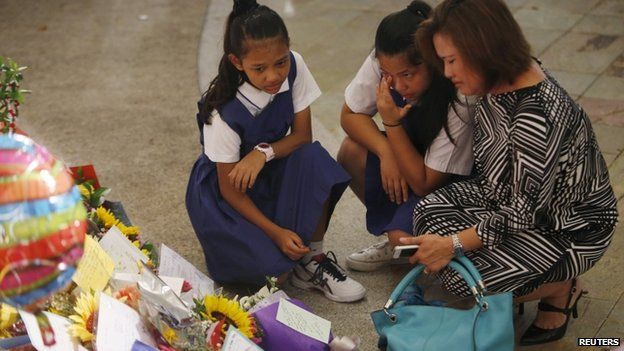 A woman and her daughters cry as they mourn the passing of former Singaporean prime minister Lee Kuan Yew, at Singapore General Hospital on 23 March 2015