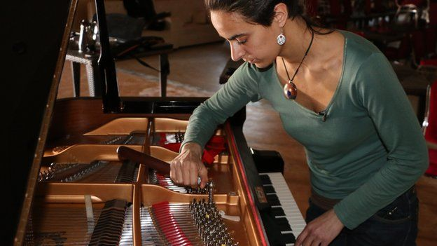 A woman tuning a piano