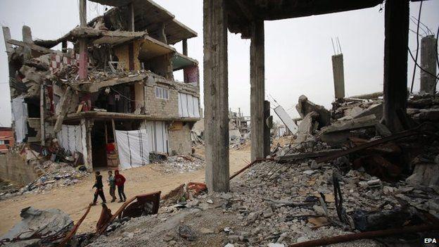 Palestinians walk past destroyed buildings in Gaza City's Shejaiya district (23 February 2015)