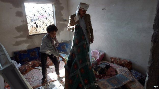 Yemeni man and boy clear up inside their home after Saudi-led coalition air strike in Sanaa (26 March 2015)